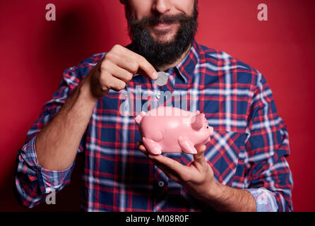 Unrecognizable man inserting coin into piggy bank - Stock Photo