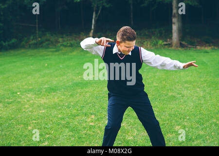 A boy, teenager, schoolboy dressed up in formalwear imitates a fight in front of a forest on a lawn in summer. - Stock Photo
