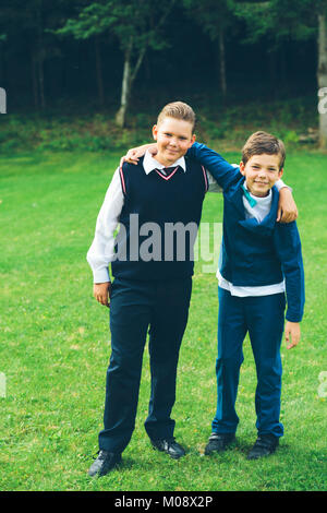 Two boys, brothers, schoolboys dressed up in formalwear with arms around each other in front of a forest on a lawn - Stock Photo
