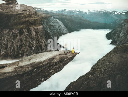 Couple Man and Woman on Trolltunga cliff in Norway above clouds Love and Travel emotions Lifestyle concept. Young - Stock Photo