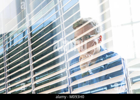 Casual businessman working in office, sitting at desk, typing on keyboard, looking at computer screen. - Stock Photo