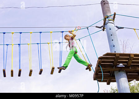 A teenage girl confidently moves on swinging boards at a height in a rope park. Courage and overcome - Stock Photo