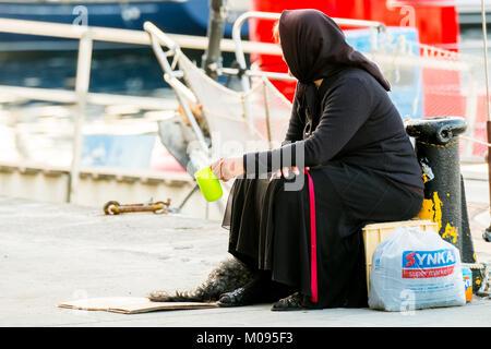 beggar woman in black robe in port of Chania, poverty, Europe, Crete, Greece, Chania, Europe, Crete, Greece, GR, - Stock Photo