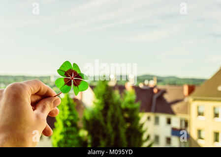 Closeup of a four leaf lucky clover held by a hand against skyline as template - Stock Photo