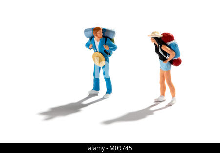 Miniature figures of two travellers or backpackers on a white background with shadows standing looking at each other - Stock Photo