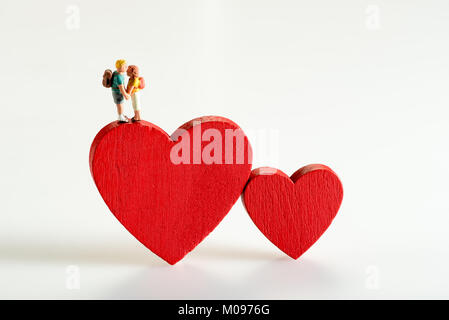Miniature figures of two young people in a relationship holding hands standing on a red heart symbolic of love , - Stock Photo