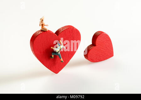 Miniature man climbing a red heart to reach a beautiful young lady on top in a concept of love, romance and Valentines - Stock Photo