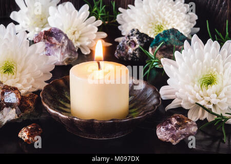 White Candle with White Chrysanthemum Flowers and Garnet, Amethyst, Ruby and Turquoise. - Stock Photo