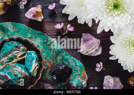 Rough Amethyst, Turquoise, Garnet in Matrix and Onyx with Mixed Flowers on Dark Table - Stock Photo