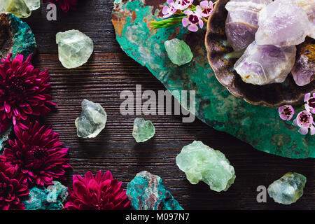 Rough Amethyst, Fluorite and Turquoise with Mixed Flowers on Dark Table - Stock Photo