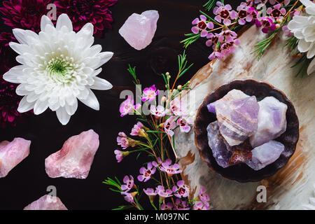 Rough Amethyst and Rose Quartz with Chrysanthemums and Pink Flowers on Dark Table and Pink Flowers on Dark Table - Stock Photo