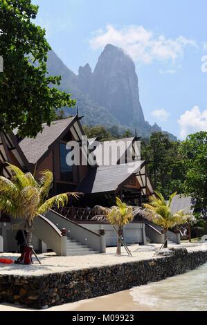 Tunamaya Beach & Spa Resort chalets with mountain towering in background - Tioman Island, Malaysia - Stock Photo