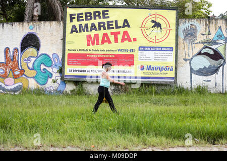 Sao Paulo, Brazil. 19th Jan, 2018. A woman walks past a sign which invites citizens to ger vaccinated against yellow - Stock Photo