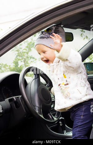 Cute little girl driving car. Child sitting in big car - Stock Photo