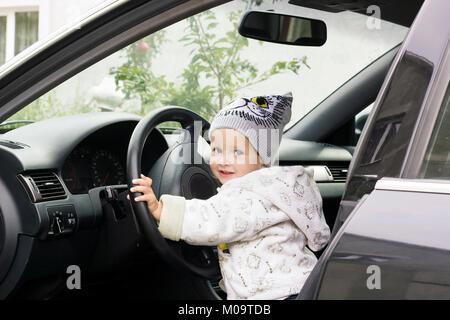 Cute little girl driving car. Child sitting in big car - Stock Photo