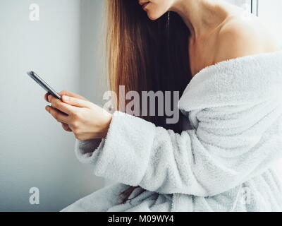 Young, sweet woman in a white bathrobe communicates on a mobile phone during a break between spa treatments - Stock Photo