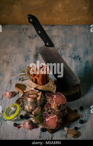 Vertical photo of stacked pieces of dried smoked meat from italian wild boar. Meat is on vintage chopping board - Stock Photo
