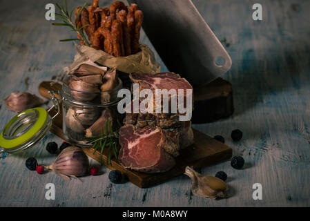 Horizontal photo of stacked pieces of dried smoked meat from italian wild boar. Meat is on vintage chopping board - Stock Photo