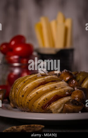 Vertical photo of two roasted whole potatoes on white plate. The vegetable is cut on slices which are filled by - Stock Photo