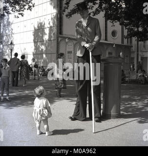 1950s, historical, 'who's looking you kid....a toddler looks up in wonder at an extremely tall man, a stiltwalker, - Stock Photo