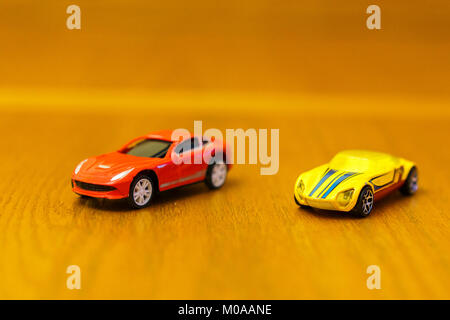 Toy cars red and yellow on a wooden background - Stock Photo