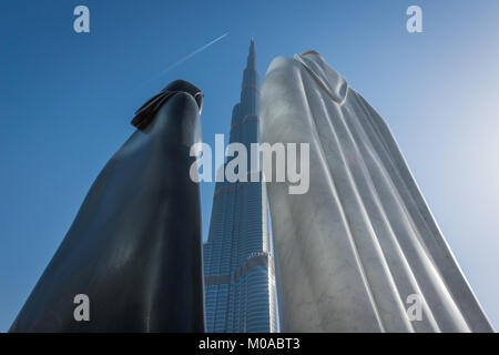 Sculpture of a traditional Gulf couple outside Burj Khalifa called 'Together' in Dubai, UAE, United Arab Emirates. - Stock Photo