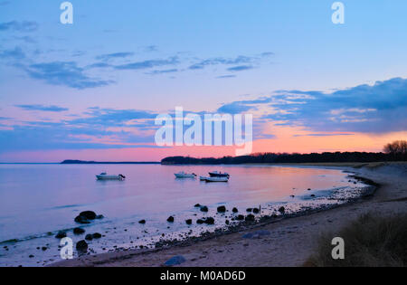Sunset over island Rugen in Baltic sea. Motor and fisherman boats by the sandy shore on a sunset - Stock Photo