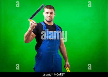 A dark-haired male construction worker in a black T-shirt and blue construction overall holds construction r L shape - Stock Photo