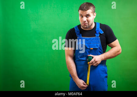 A dark-haired male construction worker wearing a black T-shirt and blue construction overall having fun, laughing - Stock Photo