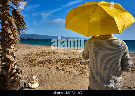 Man on a mediterranean sandy beach with a yellow umbrella in a sunny day - Stock Photo