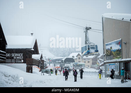 The scene at the top of the cable car above Canezei, at Belvedere, as the snow comes down. A few intrepid skiers - Stock Photo