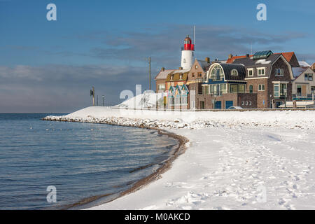 Dutch beach covered with snow and view at lighthouse Urk - Stock Photo