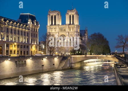Romantic Paris, illuminated Seine river and Notre-Dame cathedral at night.  Panoramic image, shallow DOF, focus - Stock Photo