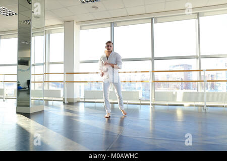 Young blonde dancer enjoys winning in white suit and makes warm  - Stock Photo