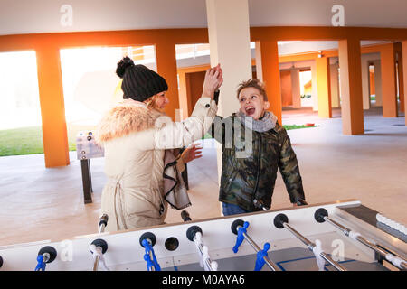 mother and son exulting after victory in the game of table football. concept of people having fun - Stock Photo