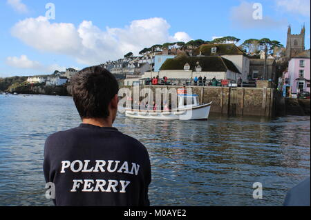 The back of the ferryman wearing a black tshirt with Polruan written on it as the ferry reaches Fowey harbour and - Stock Photo