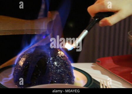 Hand with lighting igniting alcohol on Christmas pudding, resulting in blue flames - Stock Photo