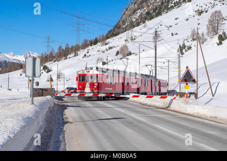 Red train of Bernina passes through a level crossing during winter trip - Stock Photo