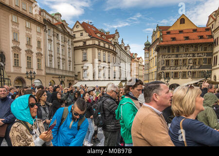 Crowds of visitors and tourists gather in front of Prague Astronomical Clock to enjoy a fascinating mechanical performance - Stock Photo