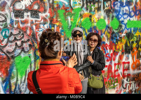 Chinese tourists posing for photographs in front of the Graffiti covered  John Lennon Wall in Prague . - Stock Photo