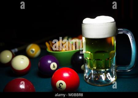 A cold beer mug on a green billiard table around a lot of billiard balls - Stock Photo