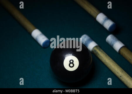 number Eight billiard ball on green billiard table with several cue sticks - Stock Photo