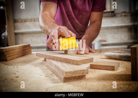 Close-up of a young strong male carpenter builder in a purple working football polishes a wooden bar using sandpaper - Stock Photo