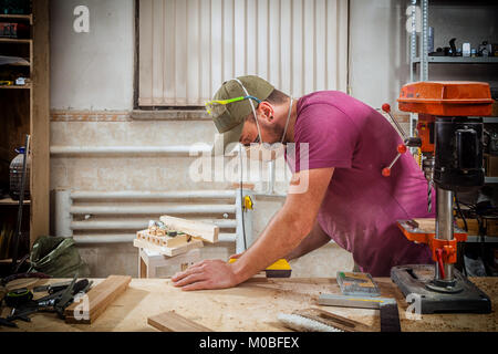 A young strong man builder carpenter works with a wooden bar for making furniture, measures and cuts in the workshop, - Stock Photo
