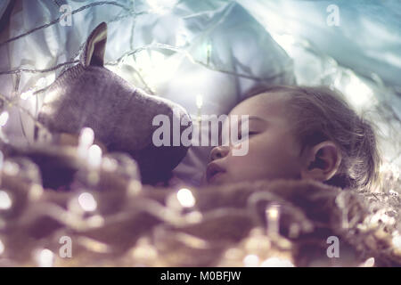 Sweet little baby boy sleeping with favourite soft toy, dreaming at home on magic night, vintage style fantasy photo - Stock Photo