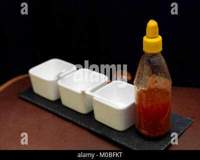Red sauce or ketchup in a plastic bottles and three empty food bowls arranged in a row, studio shot - Stock Photo