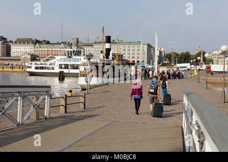 Helsinki, Finland - August 21, 2016: Tourists with luggage on the Market square shore. Here is located the pier - Stock Photo