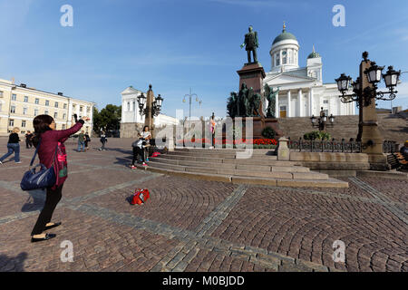 Helsinki, Finland - August 21, 2016: Chinese tourists make photos against the statue of Russian Emperor Alexander - Stock Photo