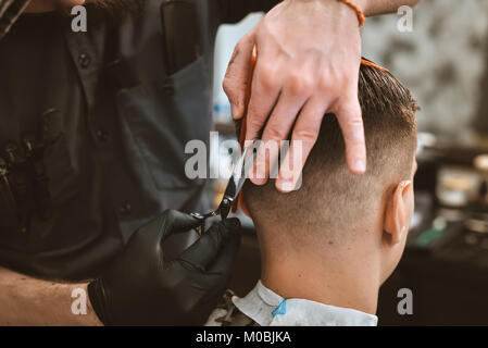 Closeup of smiling man getting an haircut from barber - Stock Photo