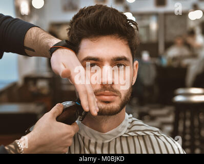 The hands of young barber making haircut to attractive man in barbershop - Stock Photo
